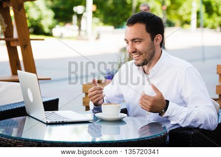 Work and relax. Online conference. Businessman dressed in shirt working with laptop, talking by skype at the park cafe outdoors.