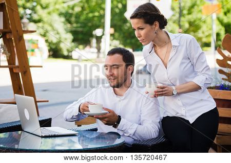Business colleagues with a laptop working in a cafe using conference internet call.
