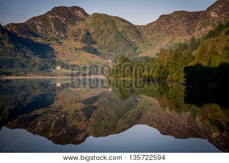 Perfectly symmetric reflections on a mirror-like lake at sunrise