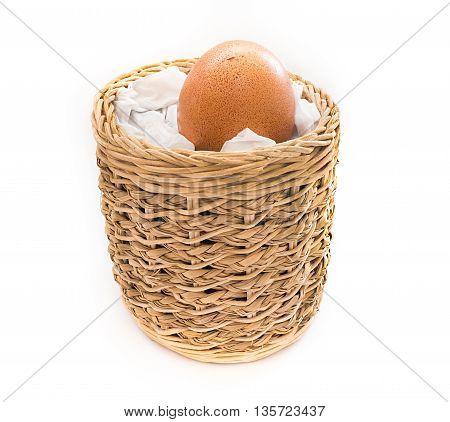 Single Egg with little bit crack in handicraft basket on white background.