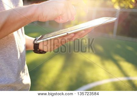 Hand holding with touch on tablet and on green grass