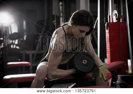 Young sexy fitness girl workout with dumbbells in the gym. Brunette fitness woman in sport wear with perfect muscular body. Backlight and toning image