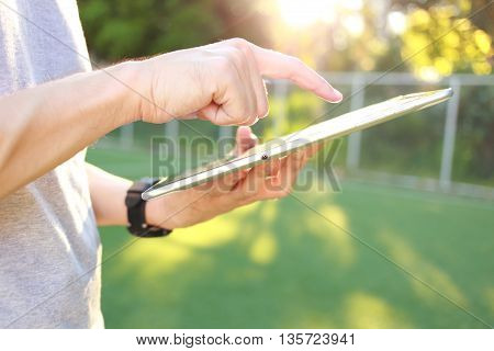 Hand holding with touch on tablet and green grass