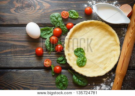 Baking a vegetables tart with tomatoes and spinach. The ingredients on the table - dough tomatoes spinach cream eggs