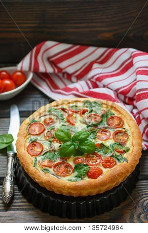 Summer outdoor tart pie of fresh vegetables - tomatoes spinach and red onion with cream and cheese. Selective focus