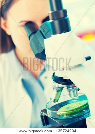 Scientist young woman using a microscope in a science laboratory. Toned photo