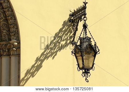 Ancient lantern in a metal frame hanging on the wall of the town Church.