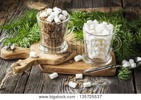 Winter breakfast ingredients. Chocolate oat cereal with marshmallows in portioned glass mugs for a cozy winter holiday nice breakfast on a background of green fir branches on prostos gray wooden background.