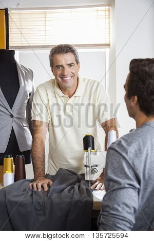 Male Tailor Leaning On Workbench In Factory