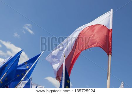 Flags of Poland and European Union Flying against the sky sunlit