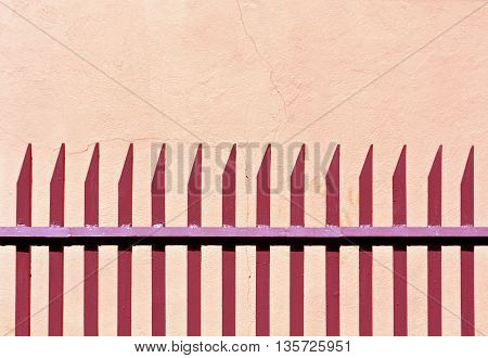 Red Metal Fence And Plaster Wall.