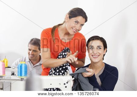 Tailor Pointing While Discussing With Colleague In Factory