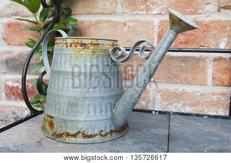A old rusting watering can on a shelf.