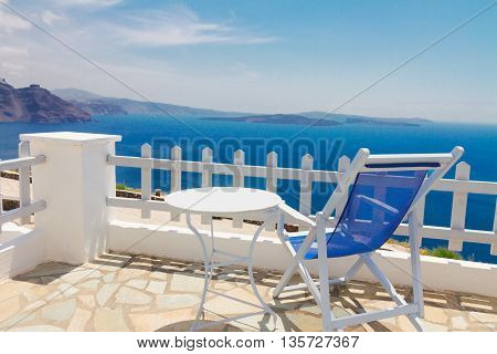 relaxing blue chair with table and view of volcano caldera, Santorini, Greece