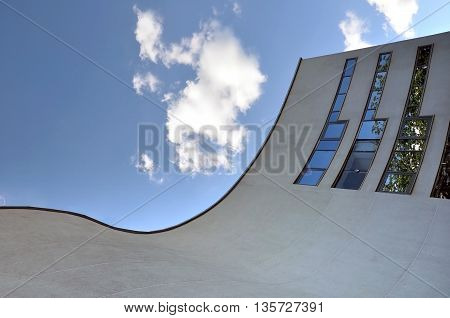 Grodno, Belarus - June 22 2016: Facade of modern Philharmonic. Concert hall with curved walls and mirrored windows. Look up.
