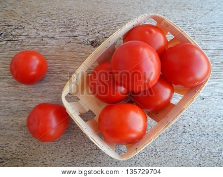 Ripe red tomatoes in rattan basket on wood background