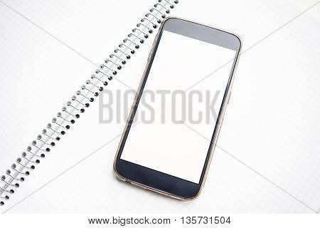 Modern smartphone mock up with white blank screen on notebook