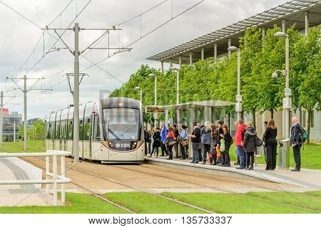 EDINBURGH SCOTLAND - JUNE 20 2016: Commuters waiting for tramcar service at Edinburgh Park to the west of the city.