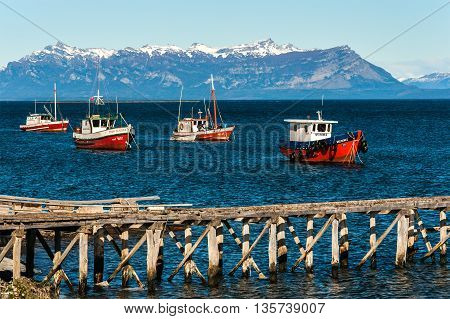 Puerto Natales Chile - April 21 2011: Colourful wooden fishing boats in the harbour at Puerto Natales port