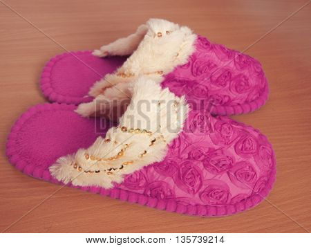 Pink slippers on wooden floor