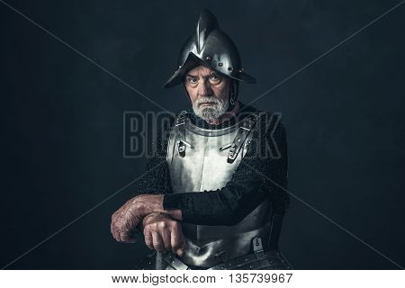 Senior with beard knight in armor holding sword.