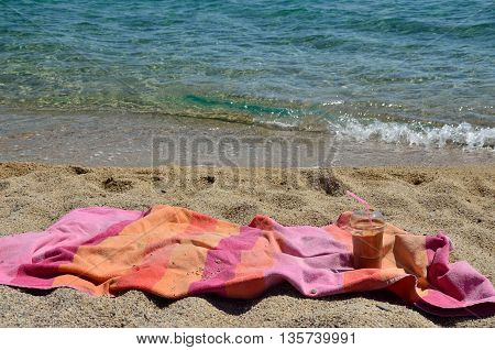 Coffee frappe and pink-orange towel on beach by the sea