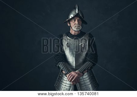 Bearded Knight Standing With Sword In Front Of Gray Wall.