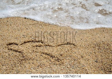 Two heart symbols written on beach sand with sea wave right behind it