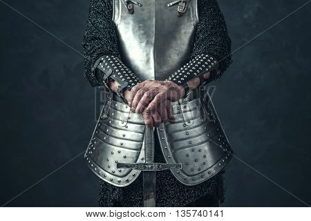 Weathered hands of knight holding a sword.