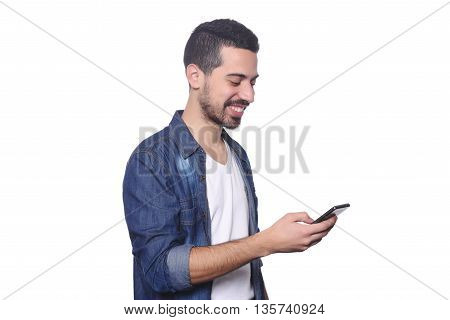 Portrait of a young latin man typing on his smartphone. Isolated white background.