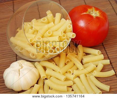 Food theme: uncooked pasta background with tomato and onion