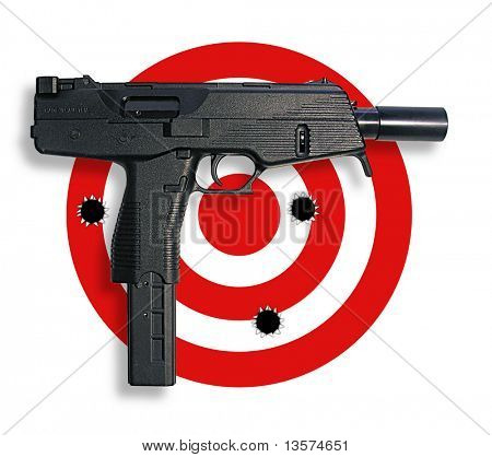 A photo of a real gun on top of target with bullet holes