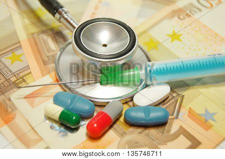 medical concept - health care costs - Stethoscope and syringe on money background and pills