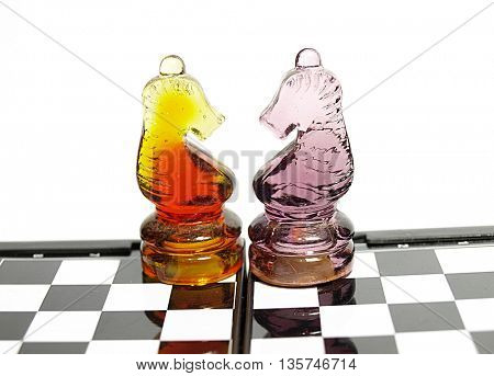 Colorful chess made of glass on chess board