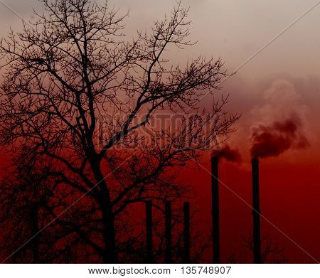 Air pollution by smoke coming out of two factory chimneys on sunset