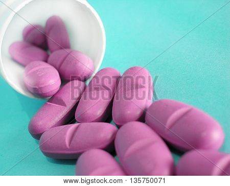 Spilled pink pills isolated on blue background