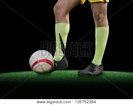 Soccer player playning kicking in ball on green grass