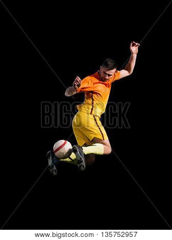 Activity soccer player in red kicking ball in jump on black background