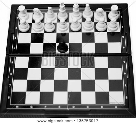 black pawn surrounded by white chess pieces on a chess board