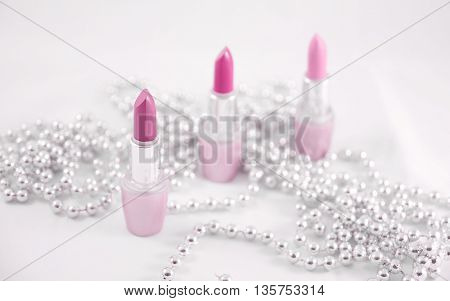 lipstick with pearls isolated on white background