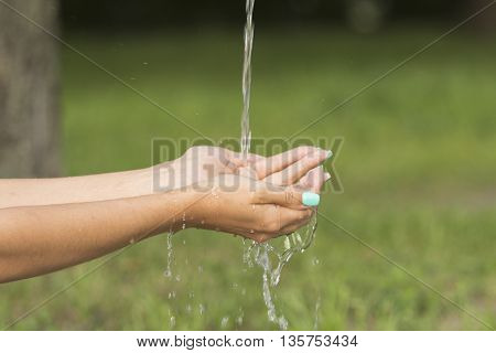 A stream of fresh clean water flowing to the hands of a girl with beautiful manicure