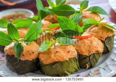 Thai steamed curry fish in banana leaf cups decorated with basil leaf (Hor Mok Pla)