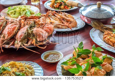 Thai style set of seafood insist of Thai steamed curry fish in banana leaf cups decorated with basil leaf (Hor Mok Pla) steamed crab/prawn/shrimp with seafood sauce