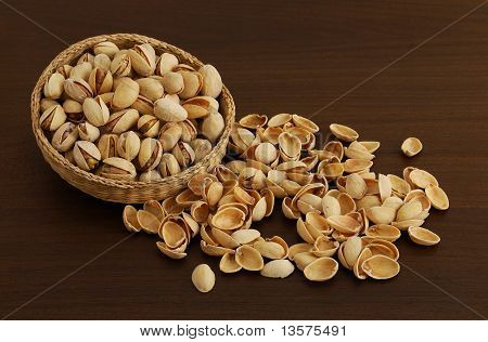 Pistachios In Interwoven Bowl With Spilled Nutshells On Dark Wooden Table