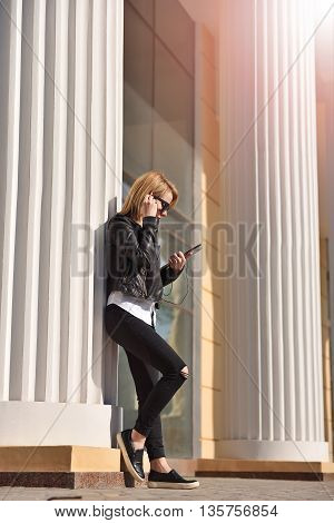 hipster girl with touch pad standing near column and listening to music