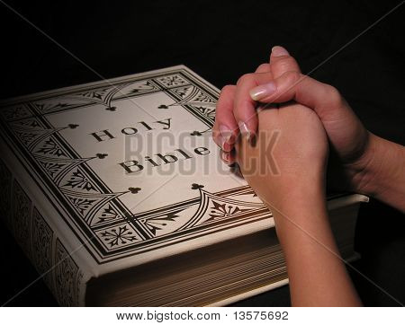 A photo of a woman praying on a bible