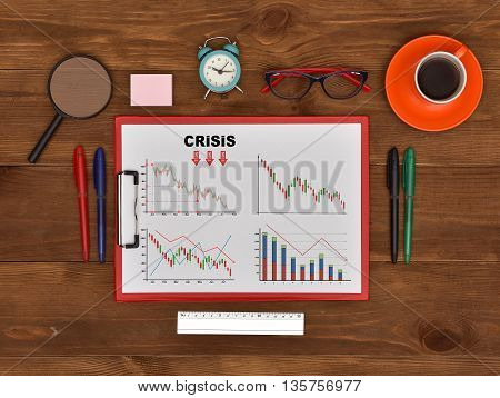 clipboard with drawing crisis chart and business objects on table