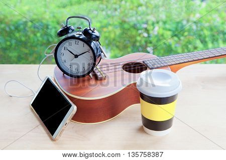 cell phone with earphone alarm clock ukulele guitar and coffee cup on wooden table in the garden. relax time concept.