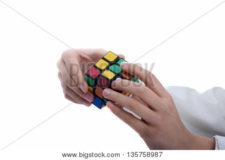 Child holding a Rubik's cube in hand on a white background