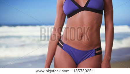 Sexy Black Woman In Swimsuit Standing With Ocean And Waves Behind Her